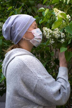 Woman in medical face mask dressed in gray smelling young white lilac bunch with buds