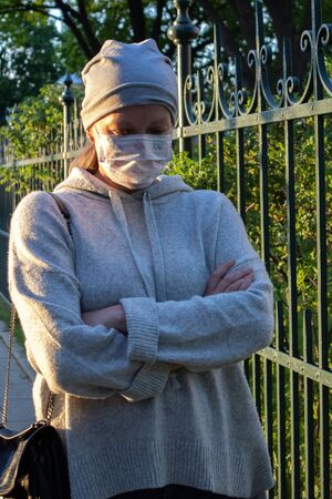 Woman in medical face mask dressed in gray with arms folded crosswise walking on the street Фото со стока