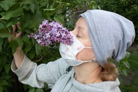 Woman in medical face mask dressed in gray smelling young violet lilac bunch with buds
