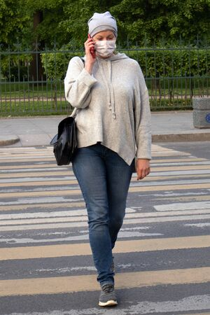 Woman in medical face mask with phone dressed in gray crossing the street