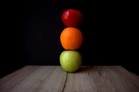 Composition of ripe tomato, green apple and orange stacked on top of each other on a wooden board Фото со стока