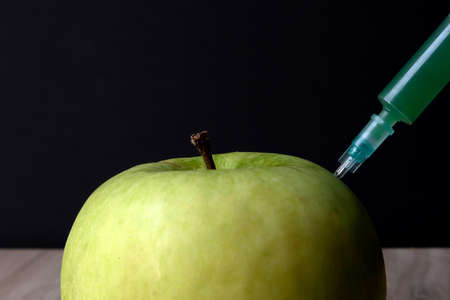 Green apple on a wooden board and syringe inside it extracting green liquid