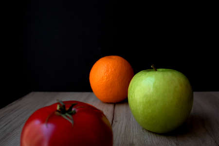 Composition of ripe tomato, green apple and orange lying on a wooden board against black background Фото со стока