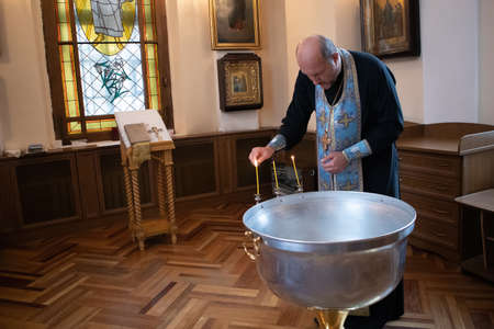 Saint-Petersburg, Russia, July 5, 2020. Priest in cassock makes preparations for christening in an Orthodox church Редакционное