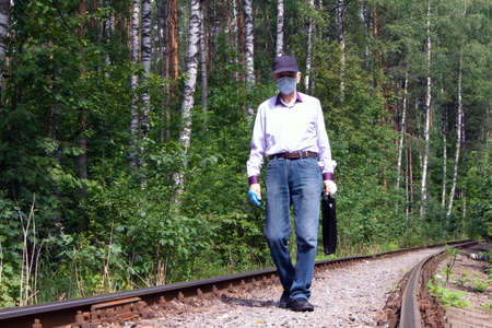 Old man in medical protective mask and latex gloves walking along old railway track