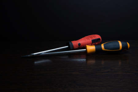 Two screwdrivers of different colors with reflection lying on a dark wooden surface Фото со стока