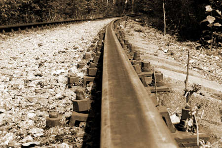 Old forest railway track with rusty rails going into the distance, sepia tone