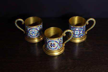 Old fashioned glass holders of brass with color enamel pattern, vintage utensil of russian soviet period