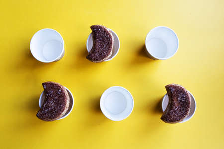 A number of semilunar candied cookies and cardboard cups organized on a bright yellow background