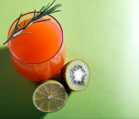 Composition of glasses with orange juice and sprig of mint leaves on a light green background