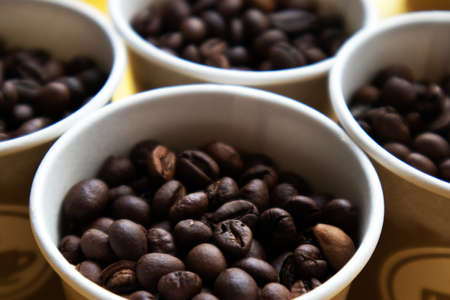 The tops of few cardboard cups full of roasted coffee beans