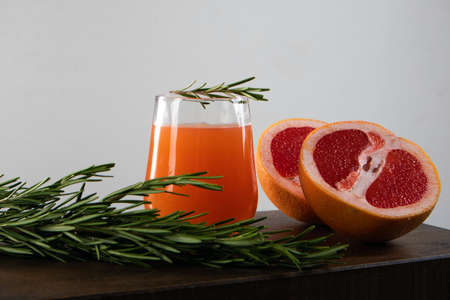 Two halves of red orange, rosemary sprig and glass of orange juice lying on a wooden table against light background Фото со стока