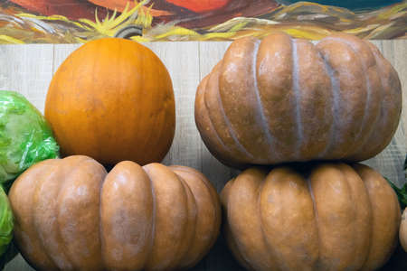 Few huge pumpkins in a storage stacked in a rows one on top of the other