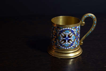 Old fashioned glass holder of brass with color enamel pattern, vintage utensil of russian soviet period Фото со стока