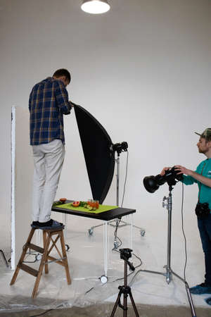 Saint-Petersburg, Russia, October 25, 2020. Food photography lesson in a photo studio, a student on a stepladder makes a flat lay