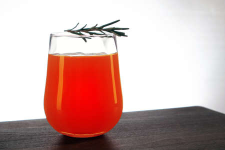 Semicircular glass of fresh orange juice with rosemary sprig on top staying on a wooden table against light background Фото со стока