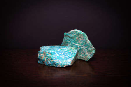 Two pieces of beautiful bright semiprecious mineral amazonite lying on a wooden surface Фото со стока