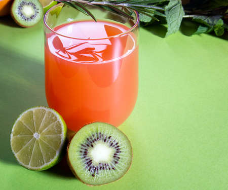 Composition of glasses with orange juice, lime, kiwi and verdure on a light green background