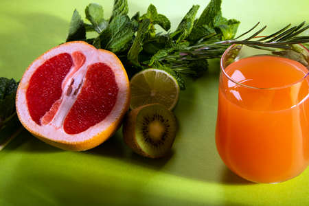 Composition of glasses with orange juice, cut red orange, lime, kiwi, rosemary and mint leaves on a light green background