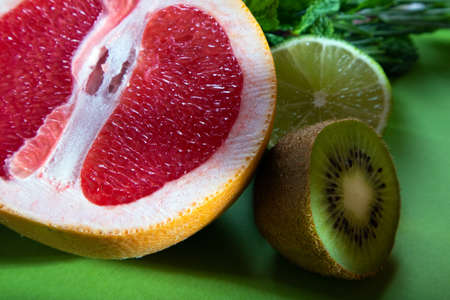 Fruit composition of cut red orange, lime, kiwi and verdure on a light green background