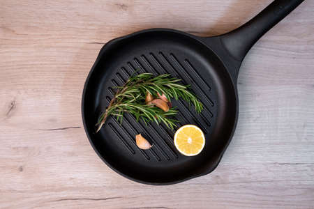 Black frying pan on a wooden board with rosemary sprigs, cloves of garlic and lemon half inside
