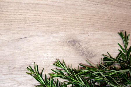 Light wooden board framed with fresh rosemary sprigs, design template Фото со стока