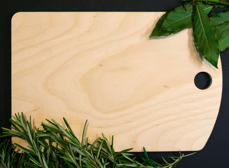 Cutting board of light wood framed with bay leaves and rosemary sprigs, designer template Фото со стока