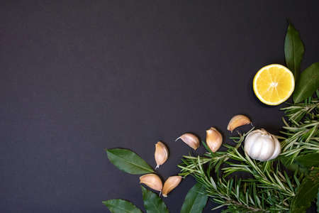 Food frame with rosemary sprigs, bay leaves, lemon half and cloves of garlic, design template Фото со стока