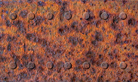 Old rusty stained metal sheet with two rows of rivets close up, metal texture or background Фото со стока