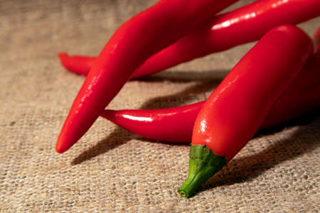 Few bright red chili peppers close up lying on a rough burlap