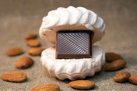 White zephyr with tile of dark chocolate inside and scattered peeled almonds lying on a sack cloth Фото со стока