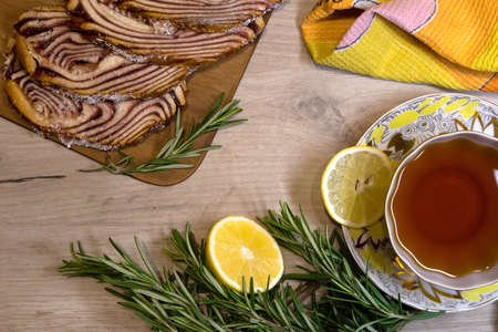 Breakfast served on a wooden table with sliced pastry roll, cup of tea, lemon half and rosemary sprigs