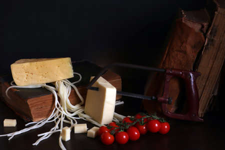 Still life with three cheeses, cherry tomatoes, old books and arm saw, absurd food photo