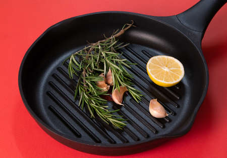 Black frying pan with rosemary sprigs and cloves of garlic inside against bright red background