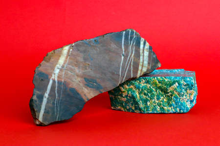 Two pieces of natural raw minerals, amazonite and jasper, against bright red background Фото со стока
