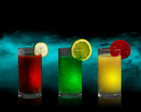 Three tall glasses with drinks of different colors and slices of lemon, tomato and cucumber