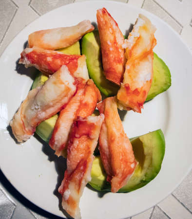 Peeled and cooked crab legs lying on a white plate with sliced ripe avocado