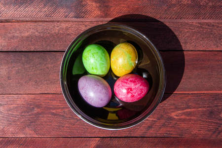 Four multicolored bright easter eggs in ceramic bowl staying on red wood surface Фото со стока