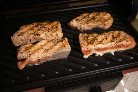 The process of frying salmon fillets at home on an electric grill