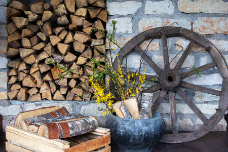 Village accessories, decorative rural scene with old cartwheel, stack of fire woods and old pot with yellow flowers Фото со стока