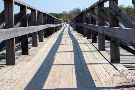 Old wooden vintage half destroyed pedestrian bridge with handrail over the lake