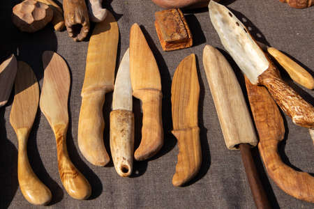 The trade tent with decorative wooden handmade knives at the open air village fair