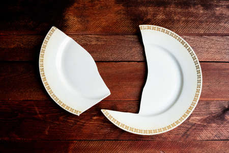 Single broken white porcelain plate with golden frame lying on a red wooden deck