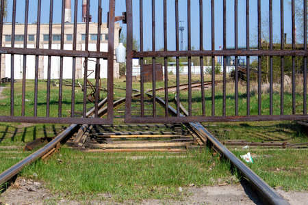 Old abandoned railroad track going into perspective behind a rusty gate