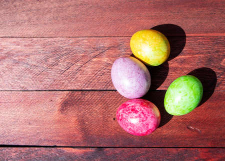 Four multicolored bright easter eggs lying on sunlit red wood deck