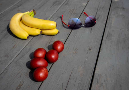 Mix composition with painted easter eggs, bunch of ripe bananas and sunglasses lying on an old wooden surface