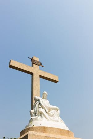 cradling: Pieta statue with cross and sky background