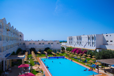 hotel building: White hotel building with a pool in summer in Tunisia