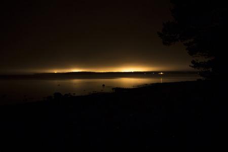 night stick: Yellow lights of a city on a coast at night Stock Photo