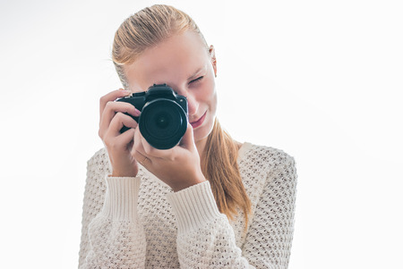 Young girl with digital camera, taking a picture isolated on white photo